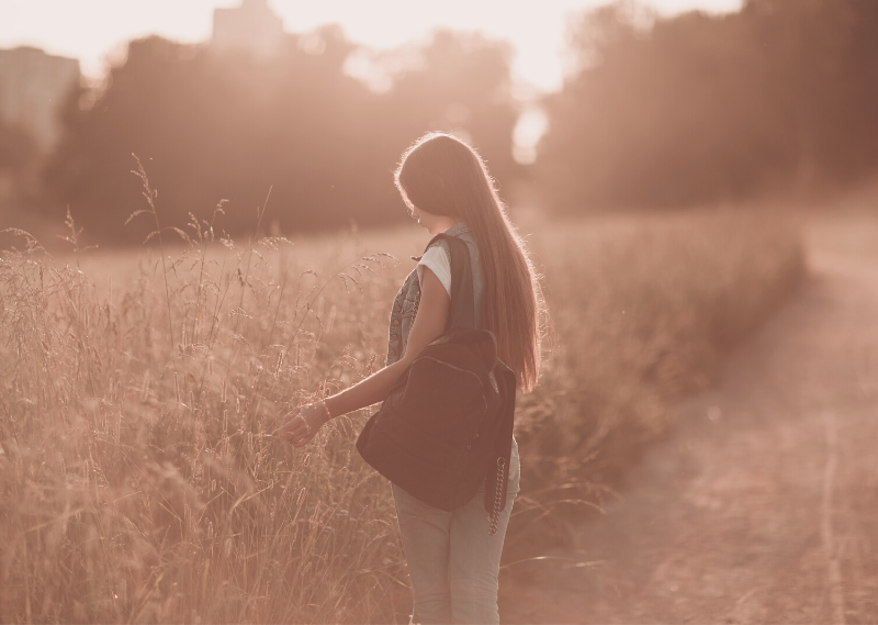 Lady walking in a field in a post about 6 simple steps to deal with stress