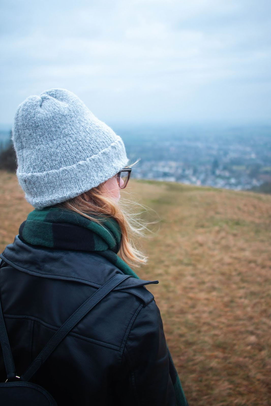 chloe harriets wearing grey beanie hat, and leather jacket looks out to scenic view - 2020 bucket list