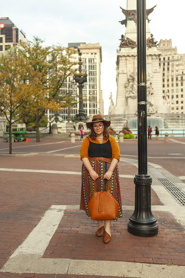 An outfit consisting of a brown panama hat, a burnt yellowish orange lace up 3/4 sleeve shirt layerd under a black camisole dress tucked under a warm patterned maxi skirt and brown d'orsay flats.