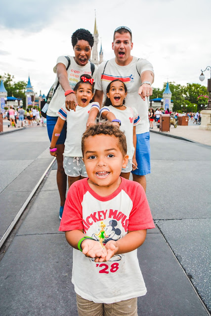 Family in matching disney t-shirts with little boy holding Tinkerbell