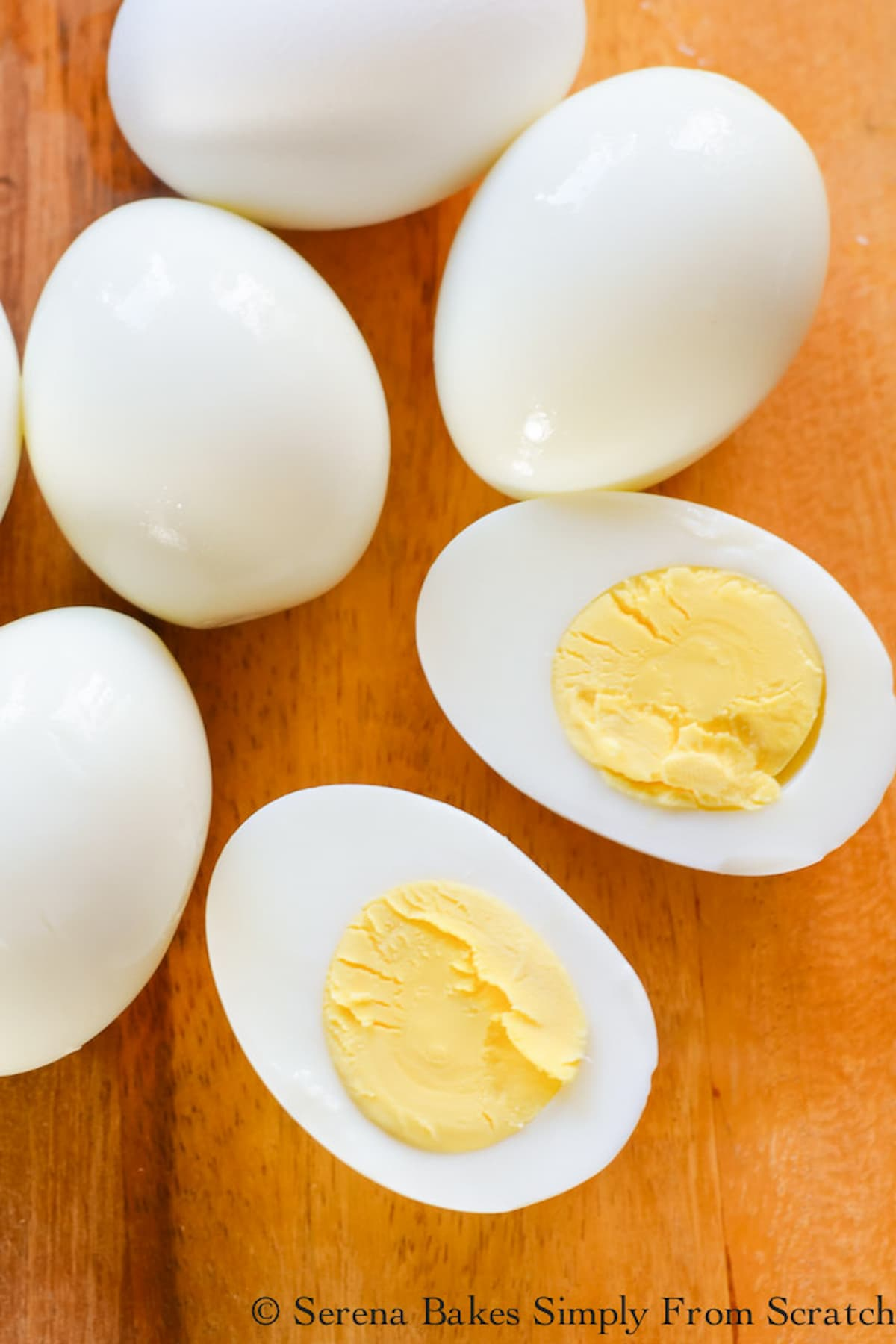 5 whole Easy Peel Whole Hard Boiled Eggs and 1 Egg cut in half to show the Yolk.