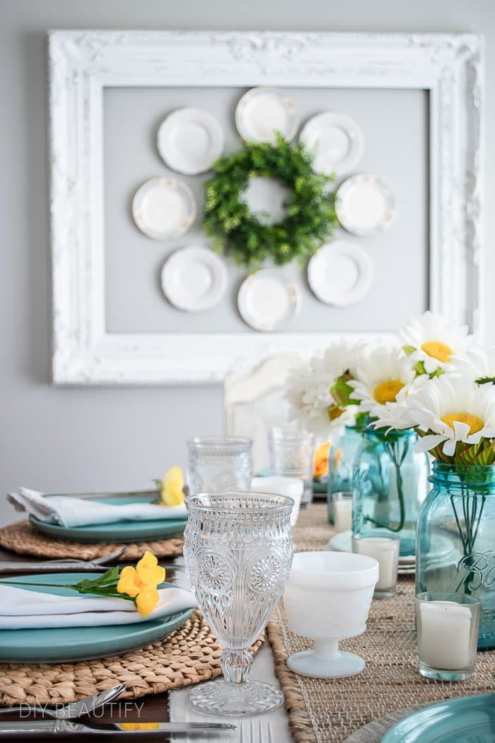 tablescape with beachy blue plates, mason jars, yellow flowers and neutral runner