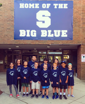 This image shows the winners of the Big Blue Pride Award for September. They are wearing their new Big Blue Pride shirts and standing under the banner outside of Swampscott Middle School.