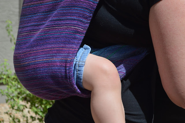 Close up image of side view of completed back carry in purple rainbow Onbu showing the seat depth just about one inch above baby's legs