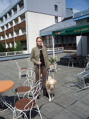 Linda stojí na terase hotelu se zlatým retrívrem v postroji