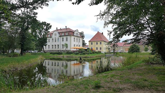 See mit Schilfrohr im Vordergrund, dahinter 2 Häuser, Rittergut und Schillerhaus