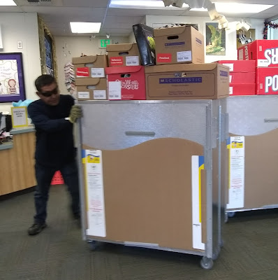 Man wearing dark shirt and pants, with dark sunglasses on, pushes metal cabinet into place next to a second cabinet. Several boxes with the Scholastic Book Fair logo are balanced on top of each cabinet.