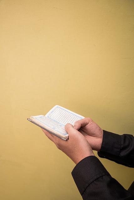Foto tangan sedang memegang Al-Quran
