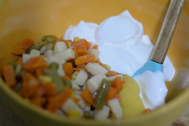 Mixing the can of mixed vegetables and sour cream together in a yellow bowl with a rubber spatula.