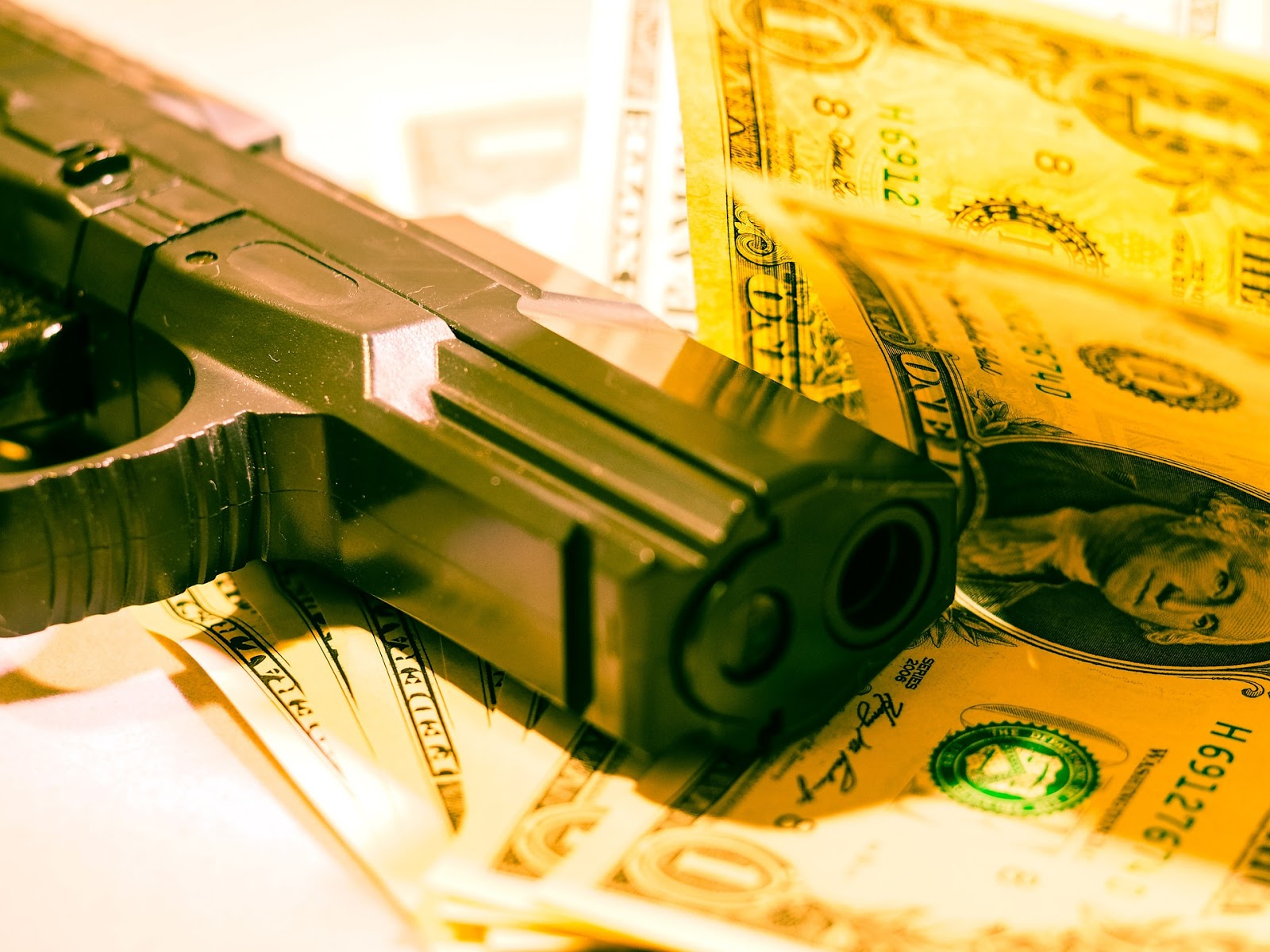 close up of several 1 dollar bills and the barrel of a pistol to illustrate blog post about movie den of thieves