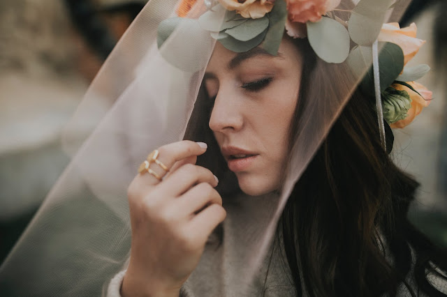 Brunette girl wearing a veil, flower crown, and gold rings.