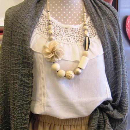 Blusa blanca con volante, collar flor y echarpe gris