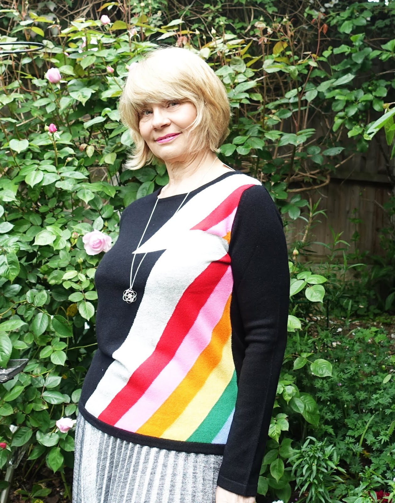 Black cashmere jumper with Bowie stripe worn in an English garden by a female style blogger in silver pleated skirt