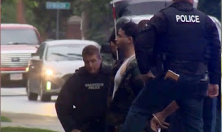 A suspect is taken into custody as Massachusetts state police respond to group of armed men blo.
