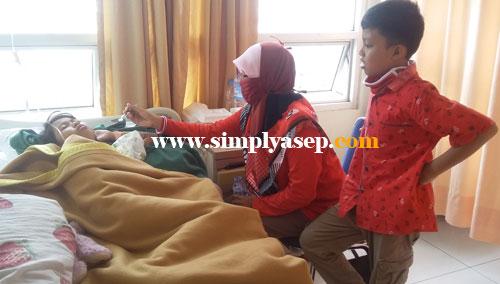 PASCA OPERASI :  Tazkia sedang disuapi oleh bundanya didampingi kakaknya Abbie di ruang kamar istirahatnya di RS UNTAN.  Foto Asep Haryono
