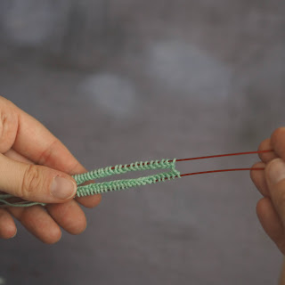 cable being pulled through the centre of mint stitches on a circular needle