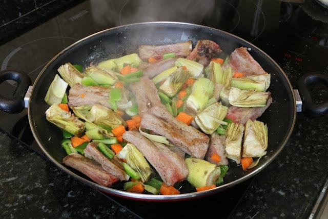 Preparación de arroz con costillas y alcachofas