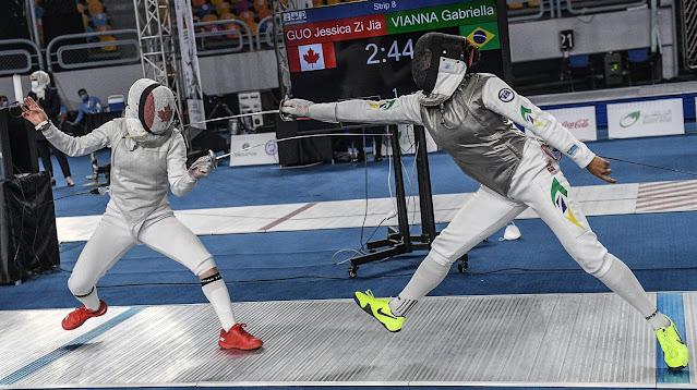 Atletas do canadá e brasil disputam torneio de esgrima. a bandeira dos países está na máscara
