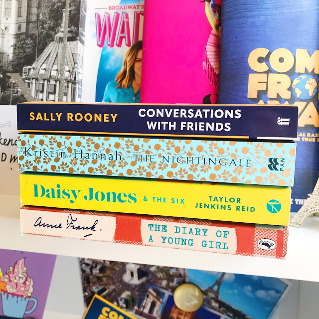 4 books stacked on desk shelf in front of musical programs