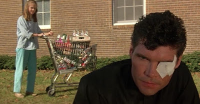 "Movie still for ""Silver Bullet"" (1985) where Megan Follows pushes a full shopping cart as she looks on at Everett McGill, a priest who has an eyepatch on"