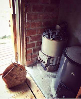 Kotakiuas ja kotapata sekä taustalla vanhoista tiilistä tehty paloseinä