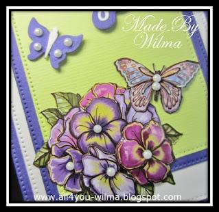 Een close-up van het 3d-plaatje van de bloemen met vlinder en een paarse gestantste vlinder met plakparels op de vleugeltjes. A close-up of the 3d-image of the flowers with a butterfly and a purple stamped butterfly with adhesive pearls on the wings.