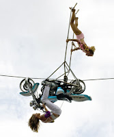 Tel üzerinde motosikletle ters giden bayan akrobatların akrobasi gösterisi