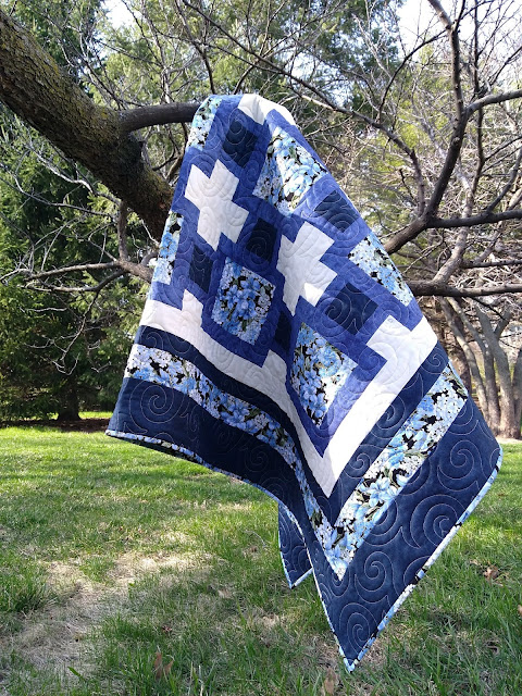 Blue and cream floral quilt hanging on tree branch