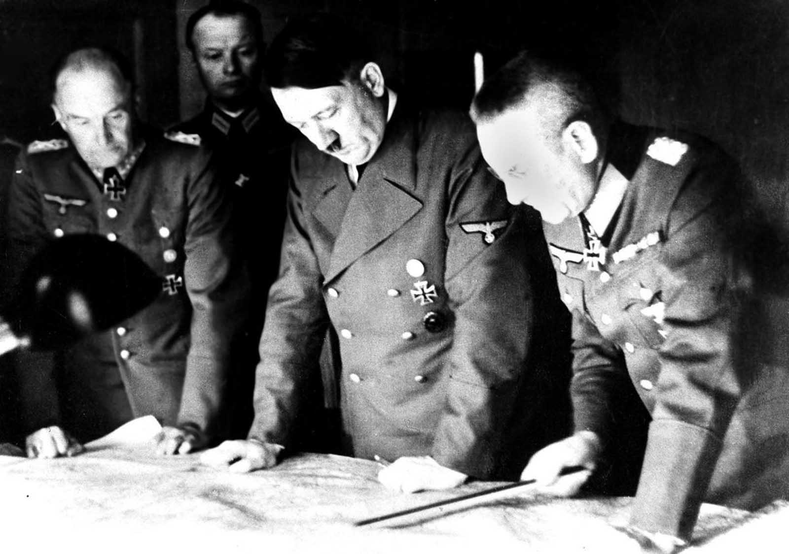 Adolf Hitler, center, studies a Russian war map with General Field Marshal Walter Von Brauchitsch, left, German commander in chief, and Chief of Staff Col. General Franz Halder, on August 7, 1941.