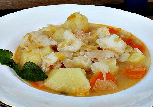 Un plato con bacalao, patatas, puerro y zanahoria. Caldoso