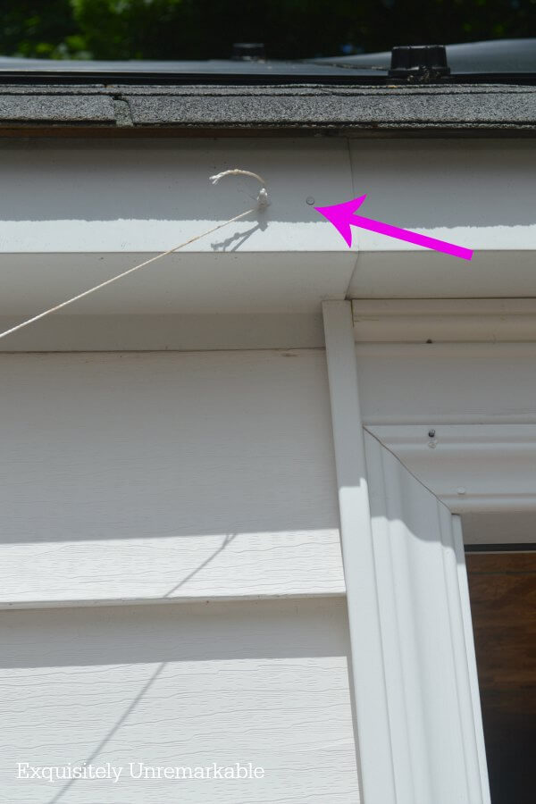 Garage door with small nails and twine attached to it