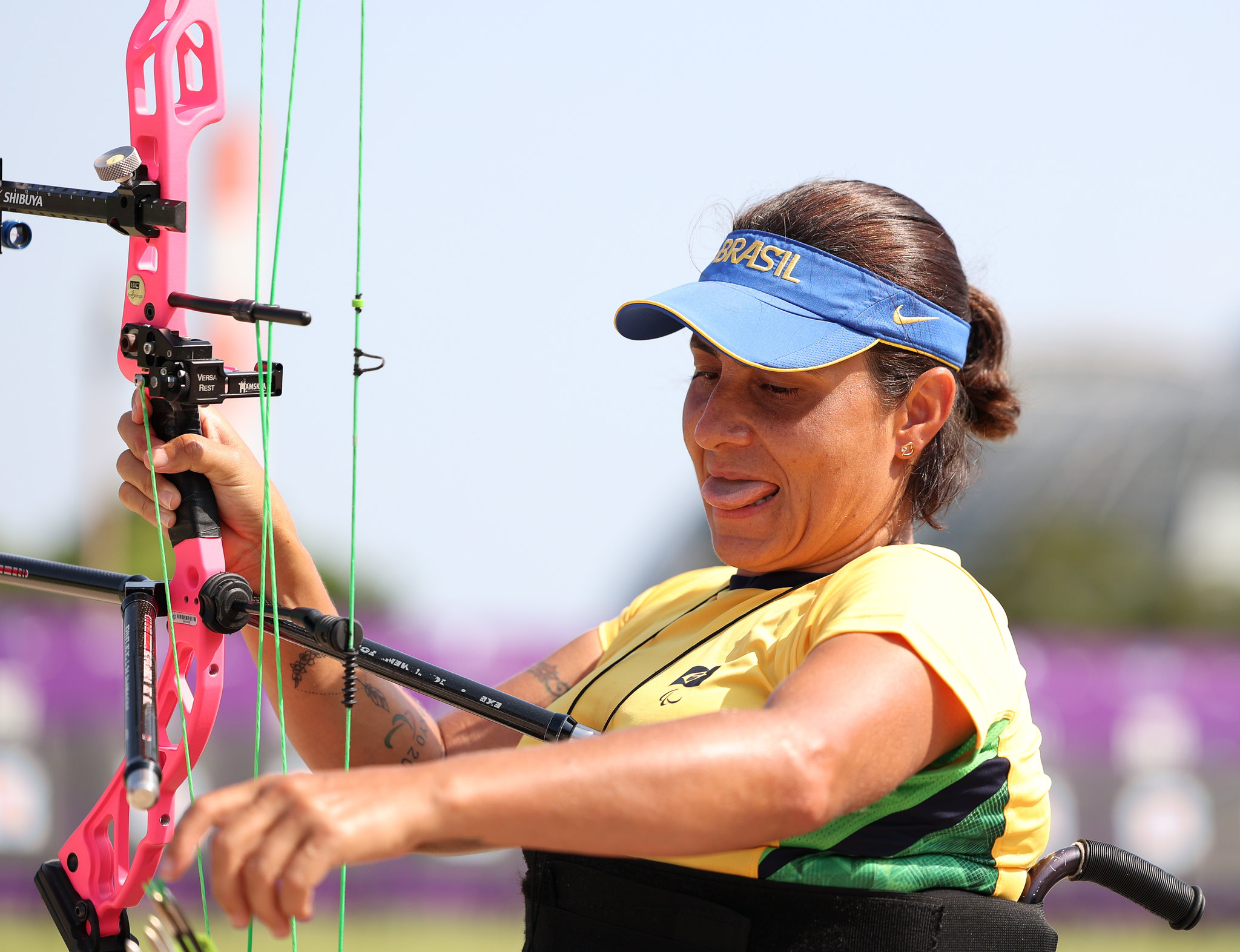 Rejane Candida da Silva mostra a língua e prepara arco e flecha