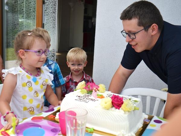 czteroletnia Zosia zdmuchuje świeczki i myśli nad życzeniem