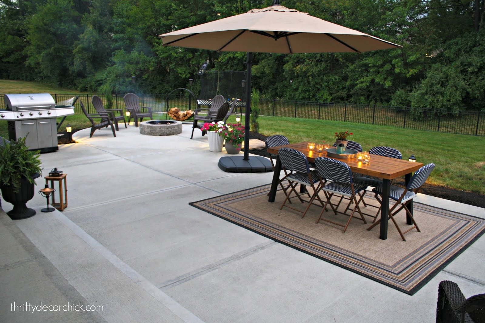 Large patio with outdoor dining and round fire pit