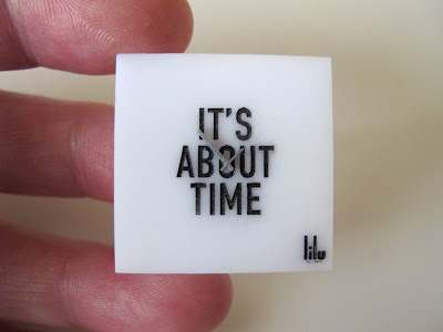Hand holding a modern dolls' house miniature square perspex clock.