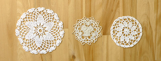 Three handmade white cotton crochet coasters next to each other a a light wood background, showing their relative sizes.
