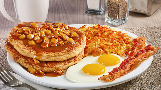 topped pancakes with eggs, bacon, and hash browns