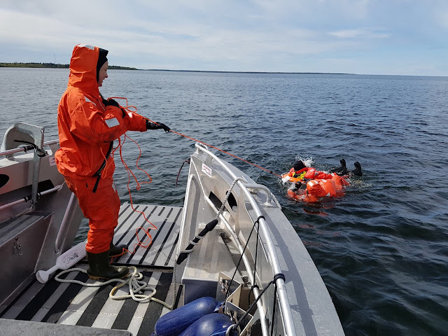 Pelastautumispukuinen henkilö hinaa kahta henkilöä veneeseen