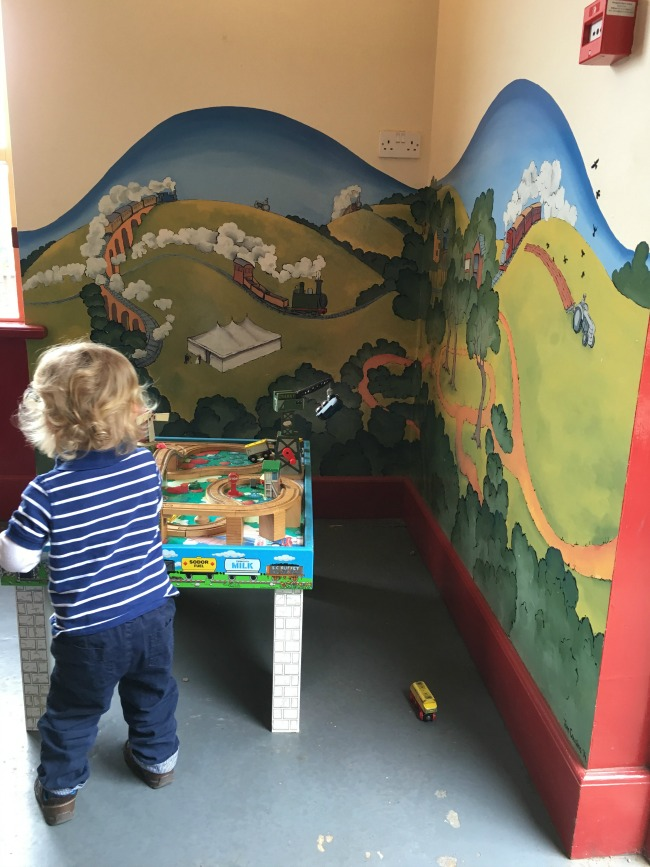 trains-and-trampolines-toddler-playing-with-train-set