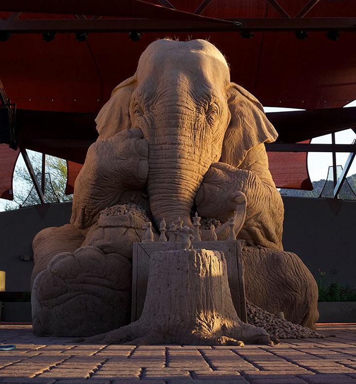 Imponente escultura de arena de un elefante de tamaño natural que juega al ajedrez con un ratón