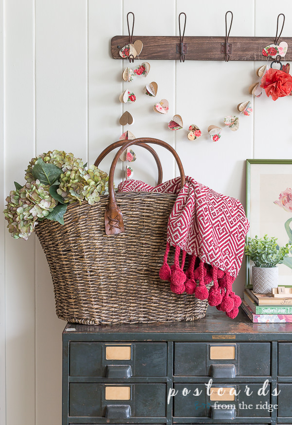 paper heart garland and woven basket tote with faux hydrangeas and red throw blanket