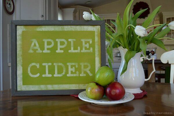 Handmade Green Apple Cider sign in white kitchen with apple and flowers on table.