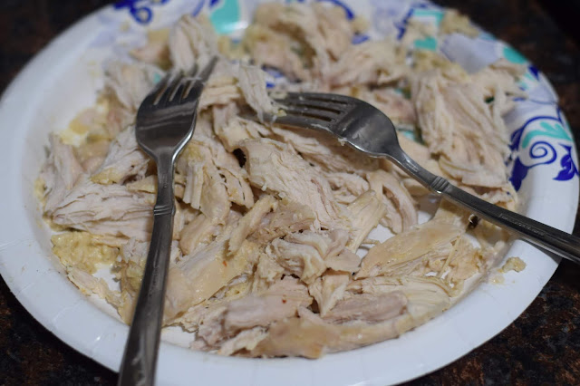 The chicken shredded on a plate with two forks.