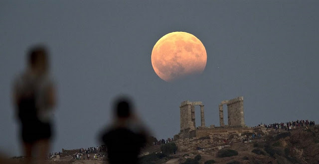 The August full moon rises above the 5th Century BC Temple of Poseidon at Cape Sounio, south of Athens, on Monday, Aug. 7, 2017. Credit: Petros Giannakouris / AP