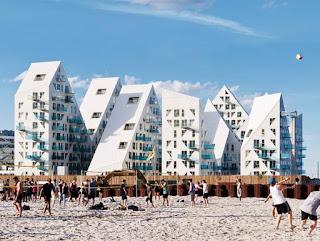 Foto. Em primeiro plano, em um dia ensolarado, um grupo de pessoas sobre a areia branca praticam esportes com bola. Ao fundo, um arrojado, ventilado e bem iluminado conjunto de torres brancas em formatos geométricos, composto por triângulos irregulares. Há janelas quadradas grandes e retangulares e triangulares menores, portas retangulares com pequenas sacadas de vidros azuis. O conjunto remete à icebergs sob um céu azul com poucas nuvens.