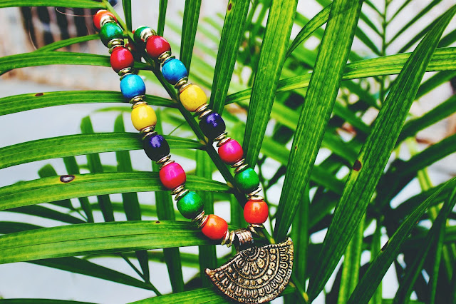 Beaded necklace hanging from a plant.