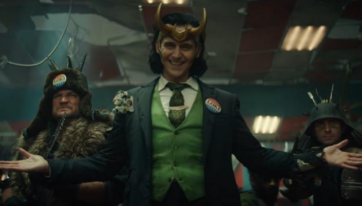 Imagem: Loki, um homem branco de cabelos pretos na altura do ombro usando uma tiara com chifres Dourado está sorrindo e estendo as mãos. Ele usa um terno verde que está todo destruído e usa um broche de eleição no seu peito que tá escrito Lock. Ao lado dele tem um homem branco com uma roupa de inverno feita de peles e segura facas. Do outro lado tem um homem usando roupa de soldado e também está com armas e o capacete é cheio de estacas.