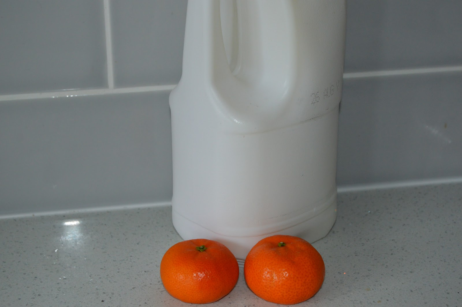 A bottle of milk and two oranges