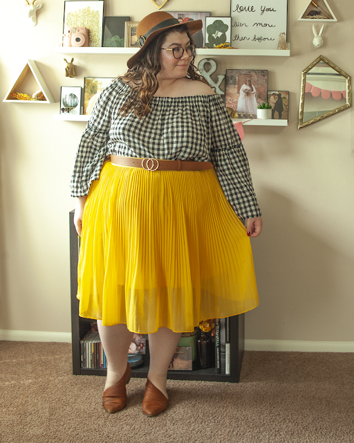 An outfit consisting of a brown panama hat, a white and black gingham off the shoulder blouse with bell sleeves, tucked into a yellow pleated midi skirt and brown d'orsay flats.