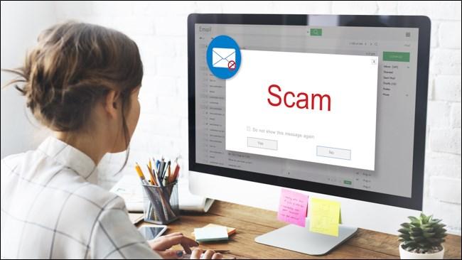"""امرأة تفتح رسالة بريد إلكتروني على جهاز الكمبيوتر الخاص بها تقول """"احتيال""""."""